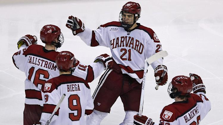 Harvard's Marshall Everson (21) is congratulated by teammates after his goal during the third period of the consolation game at the Beanpot college hockey tournament in Boston, Monday, Feb. 11, 2013. Harvard defeated Boston University 7-4 to take third place in the tournament. (AP Photo/Charles Krupa)