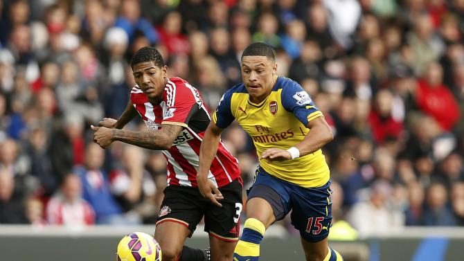Sunderland's Patrick van Aanholt challenges Arsenal's Alex Oxlade-Chamberlain during their English Premier League soccer match at the Stadium of Light in Sunderland