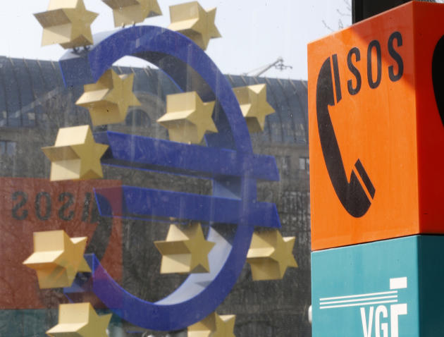 An emergency phone at a tram stop stands next to the Euro sculpture in front of the European Central Bank in Frankfurt, Germany, Thursday, March 6, 2014. The European Central Bank has kept its main in