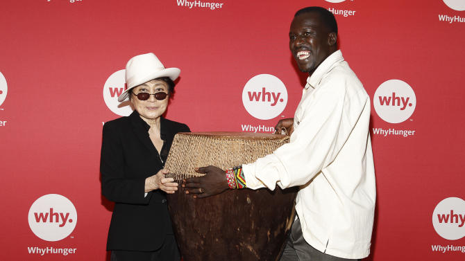 """IMAGE DISTRIBUTED FOR WHY HUNGER - Okello Sam, right, founder of Hope North, Uganda, part of WhyHunger's """"Imagine There's No Hunger"""" campaign, presents ASCAP Harry Chapin Humanitarian Award winner Yoko Ono Lennon with a handmade drum at the WhyHunger Chapin Awards on June 3, 2013 in New York. (Photo by Mark Von Holden/Invision for Why Hunger/AP Images)"""