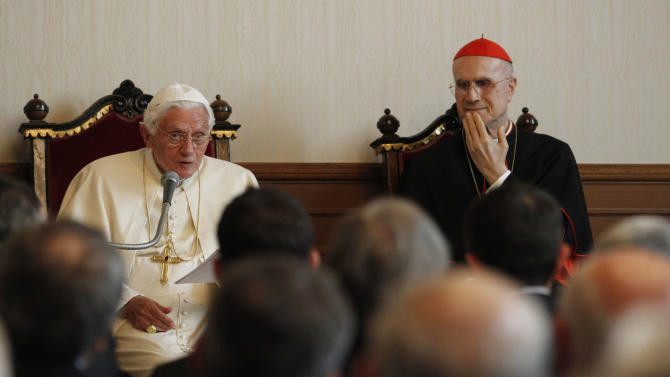Pope Benedict XVI, flanked by Vatican secretary of state cardinal Tarcisio Bertone, right, meets Milan's authorities and entrepreneurs at the archbishopric in Milan, Italy, Saturday, June 2, 2012. The pope in in Milan for the seventh World Encounter of Families, a welcome pastoral respite from an embarrassing and damaging leaks scandal at the Vatican that has engulfed the pontiff's personal butler. (AP Photo/Luca Bruno,Pool)