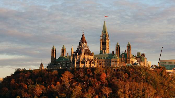 The sun sets on Parliament Hill as seen across the river from Ottawa, Ontario, in Gatineau, Quebec, Wednesday Oct. 22, 2014. A gunman opened fire at the National War Memorial, killing a soldier, then moved to nearby Parliament Hill and was shot and killed by Parliament's sergeant-at-arms. (AP Photo/The Canadian Press, Fred Chartrand)