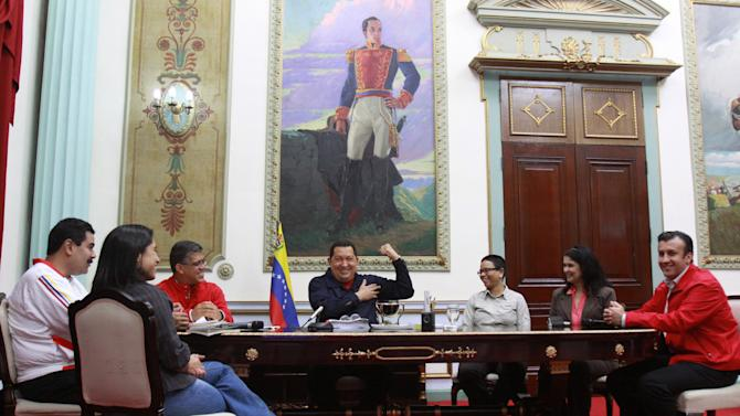 In this photo provided by the Miraflores Presidential Press Office, Venezuelan President Hugo Chavez, center, flexes his muscle during a meeting with ministers, Thursday March 29, 2012 in Caracas, Venezuela. Chavez returned home from Cuba Wednesday night shortly before midnight after a five day round of radiation therapy and says the cancer treatments are going well during a state television program early Thursday. (AP Photo/Miraflores Presidential Press Office)