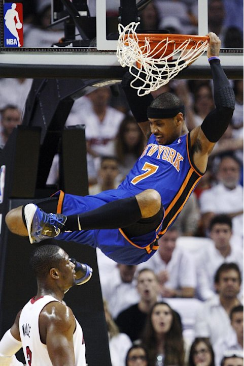 New York Knicks forward Carmelo Anthony (7) comes down after dunking over Miami Heat guard Dwyane Wade during the first half of an NBA basketball game in the first round of the Eastern Conference play