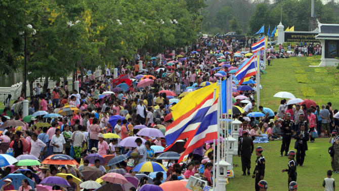 Thai residents pack on the ground near the site where King Bhumibol Adulyadej to pay a visit in Ayutthaya province, central Thailand, Friday, May 25, 2012. Thousands of Thais lined the roads from Bangkok to the historic capital Ayutthaya to catch a glimpse of the country's 84-year-old monarch as he makes his first trip outside the city since being hospitalized in 2009. (AP Photo)