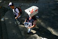 "A man walks carrying a heap of newspapers on his head in Caracas. Hugo Chavez pledged to become a ""better president"" and work with the opposition after winning a tough re-election battle that betrayed simmering discontent at his socialist revolution"