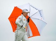 Shin Jiyai of Korea holds an umbrella during the final round of the Women's British Open golf tournament at the Royal Liverpool Golf Club in Hoylake. Shin won the Women's British Open on Sunday by a huge nine shots for her second triumph in the event