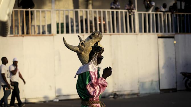 A reveller wearing a papier mache mask representing a cow takes part in the Carnival 2016 parade in Port-au-Prince