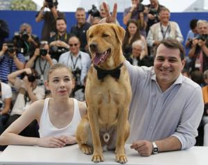 "Director Mundruczo and cast member Psotta pose with a dog sitting on the desk during a photocall for the film ""Feher isten"" in competition for the category ""Un Certain Regard"" at the 67th Cannes Film Festival"