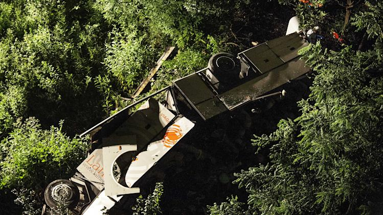 A bus lies on its side after plunging off a highway near Avellino, southern Italy, eraly Monday, July 29, 2013. A tour bus filled with Italians returning home after an excursion plunged off a highway into a ravine in southern Italy on Sunday night after it had smashed into several cars that were slowed by heavy traffic, killing at least 37 people, said police and rescuers. Flashing signs near Avellino, outside Naples, had warned of slowed traffic ahead along a stretch of the A116 autostrada, a major highway crossing southern Italy, before the crash occurred, said highway police and officials, speaking on state radio early Monday. They said the bus driver, for reasons not yet determined, appeared to have lost control of his vehicle. (AP Photo/Salvatore Laporta)