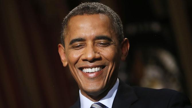 In this photo taken Friday, Oct. 4, 2013, President Barack Obama smiles during an exclusive interview with The Associated Press in the White House library in Washington, four days into a partial shutdown of the federal government that has forced 800,000 people off the job, closed national parks and curbed many government services. The deadline for keeping the government open coincided with the Oct. 1 start of sign-ups for the insurance markets at the center of the health care overhaul Obama signed into law during his first term. Government websites struggled in the first week to keep up with high demand for the new marketplaces. It's not clear that more than a few managed to enroll the first day. (AP Photo/Charles Dharapak)