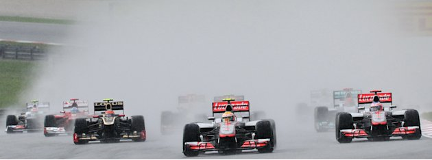 McLaren-Mercedes driver Lewis Hamilton of Britain (C) takes the lead during Formula One's Malaysian Grand Prix at the Sepang International Circuit in Sepang on March 25, 2012.    AFP PHOTO / ROSLAN RA