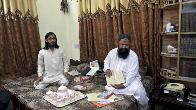 File photo of Leader of the Lashkar-e-Jhangvi Ishaq sitting on a bed with his son Malik Usman as he shows a book during an interview with Reuters at his home in Rahim Yar Khan in southern Punjab province