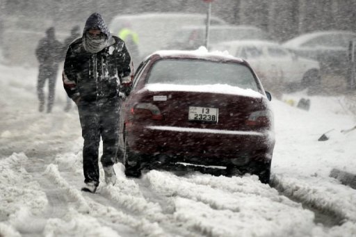 <p>A Jordanian man walks past a vehicle as snow falls over Amman on January 9, 2013. The worst storms in a decade left swathes of Israel and Jordan under a blanket of snow and parts of Lebanon blacked out, bringing misery to a region accustomed to temperate climates.</p>