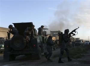 Afghan policemen arrive at the site of an attack in…