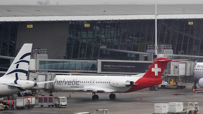 Baggage carts make their way past a Helvetic Airways aircraft from which about $50 million worth of diamonds were stolen on the tarmac of Brussels international airport Tuesday, Feb. 19, 2013. Eight armed and masked men made a hole in a security fence at the airport, drove onto the tarmac and snatched the diamonds from the hold of the Swiss-bound plane without firing a shot, authorities said Tuesday. (AP Photo/Yves Logghe)