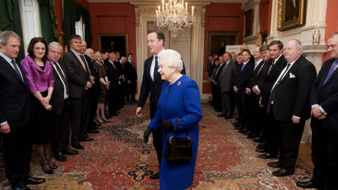 Britain's Queen Elizabeth II, center, is accompanied by Britain's Prime Minister David Cameron, center back, as she is presented to members of the Cabinet at 10 Downing Street, London, Tuesday, Dec. 18, 2012. Queen Elizabeth II sat in on a Cabinet meeting for the first time on Tuesday, taking a seat between British Prime Minister David Cameron and Foreign Secretary William Hague to observe the weekly discussion of government business. (AP Photo/Jeremy Selwyn, Pool)
