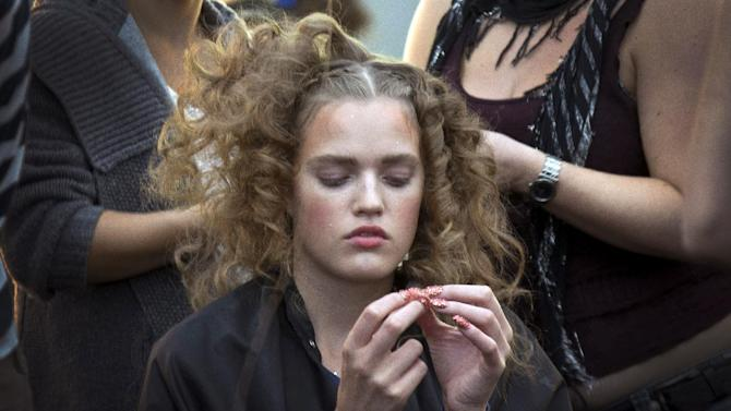 A model sits as preparations are made backstage ahead of the Spring/Summer 2013 Meadham Kirchoff collection at a central London venue, during London Fashion Week, Tuesday, Sept. 18, 2012. (AP Photo/Joel Ryan)
