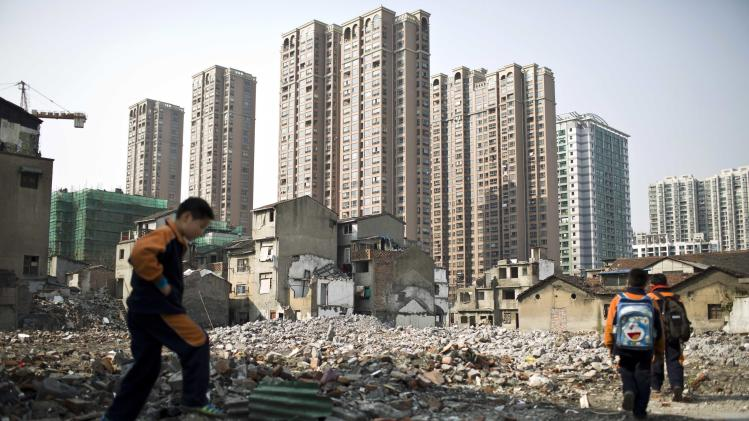 Pupils walk in an area where old residential buildings are being demolished to make room for new skyscrapers in downtown Shanghai