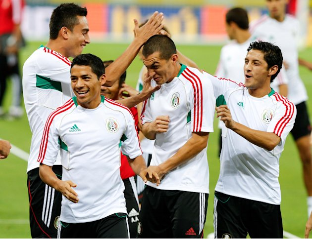 Mexico's Jorge Torres, center, is slapped by his teammates during a training session  in Fortaleza, Brazil, Tuesday, June 18, 2013. Mexico will face Brazil at the soccer Confederations Cup on June 19