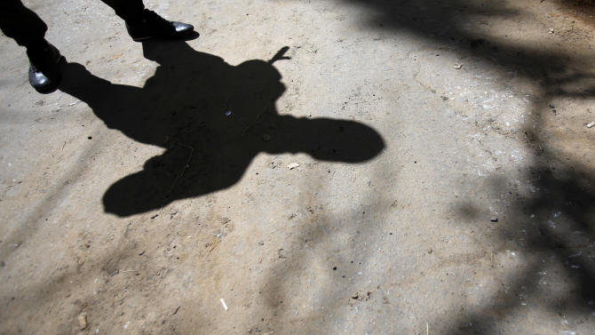 The shadow of an armed pro-Russian man while guarding the local administration building in the center of Slovyansk, eastern Ukraine, Tuesday, May 6, 2014. Interior Minister Arsen Avakov gave the death toll on his Facebook page Tuesday, adding that 20 government troops were also injured during fighting in Slovyansk, a city of 125,000, without making clear when the deaths took place. Gun battles erupted around the city Monday as the interim government tries to quell weeks of unrest in Ukraine's mainly Russian-speaking east. (AP Photo/Darko Vojinovic)
