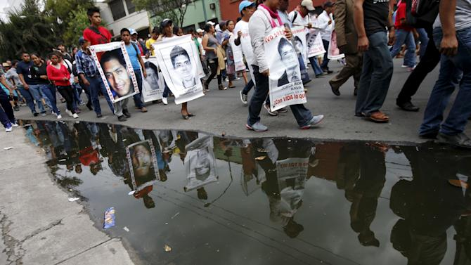 Relatives carrying photos of some of the 43 missing students of the Ayotzinapa teachers' training college are reflected in a puddle during a protest to mark the eight-month anniversary of their disappearance in Mexico City