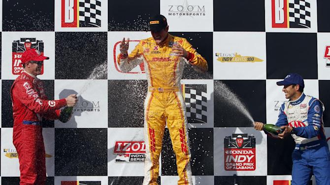 Ryan Hunter-Reay, center, is doused by Scott Dixon, left, of New Zealand, and Helio Castroneves, right, of Brazil, after winning the IndyCar Series Grand Prix of Alabama auto race in Birmingham, Ala., Sunday, April 7, 2013. (AP Photo/Butch Dill)