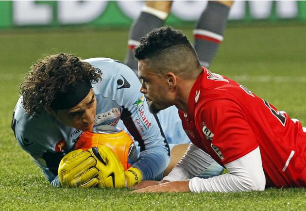 AS Monaco's Emmanuel Riviere looks at Ajaccio's goalkeeper Memo after falling during their French Ligue 1 soccer match at Louis II stadium