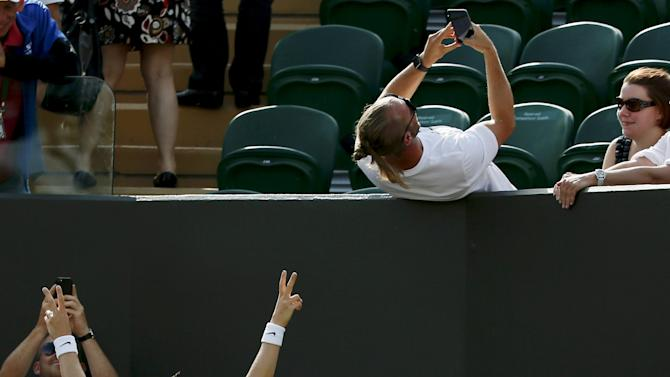 A spectator takes a selfie with Lucie Safarova of the Czech Republic after she won her match against Sloane Stephens of the U.S.A. at the Wimbledon Tennis Championships in London
