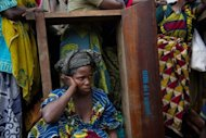 <p>A displaced Congolese woman sits amongst a crowd of people waiting for humanitarian aid in a camp for the internally displaced in Mugunga.</p>