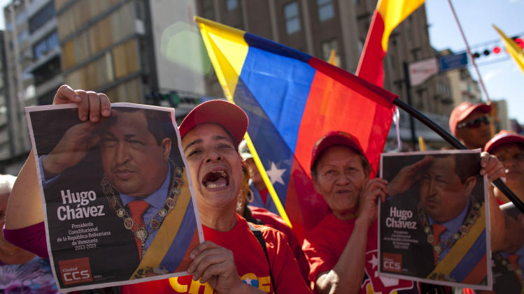 Supporters of Venezuela's president Hugo Chavez chants slogans as they hold up pictures of him during a rally in Caracas, Venezuela, Thursday, Jan. 10, 2013.  The government organized the unusual show of support for the cancer-stricken leader on the streets outside Miraflores Palace on what was supposed to be his inauguration day. The government invited leaders from across Latin America and the Caribbean to add political weight to the inauguration without an inauguree, while the country's opposition demanded details about Chavez's state and called the delay of the formal swearing-in a violation of the constitution. (AP Photo/Ariana Cubillos)