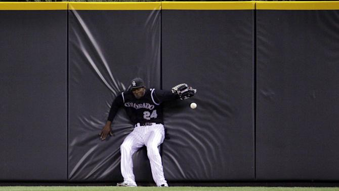 Colorado Rockies center fielder Dexter Fowler drops a fly ball hit by New York Mets' Scott Hairston in the fifth inning of their baseball game in Denver on Friday, April 27, 2012. Hairston tripled on the play and a run scored. (AP Photo/Joe Mahoney)
