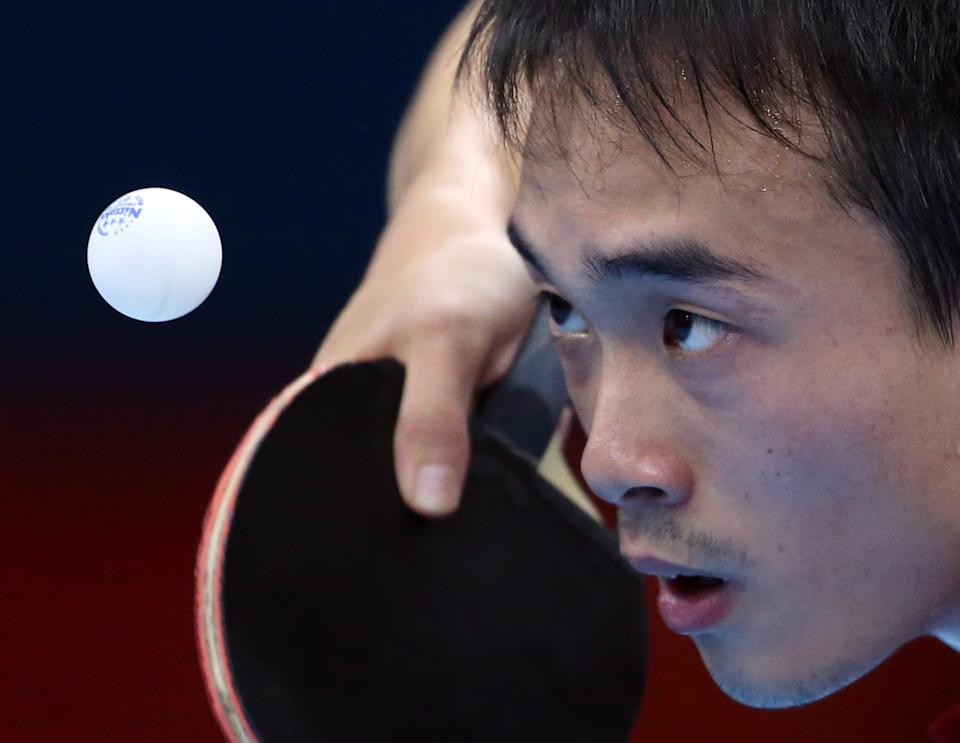 USA's Timothy Wang takes a shot against Korea's Kim Song Nam during a table tennis preliminary round match at the 2012 Summer Olympics, Saturday, July 28, 2012, in London. (AP Photo/Sergei Grits)