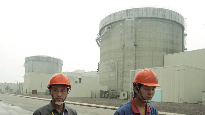 """FILE - In this June 10, 2005 file photo, workers walk past a part of Qinshan No. 2 Nuclear Power Plant, China's first self-designed and self-built national commercial nuclear power plant in Qinshan, about 125 kilometers (about 90 miles) southwest of Shanghai, China.  China is ready to approve new nuclear power plants as part of ambitious plans to reduce reliance on oil and coal, ending a moratorium it imposed because of Japan's Fukushima disaster in 2011.  The Cabinet on Wednesday, Oct. 24, 2012,  passed plans on nuclear power safety and development that said construction of nuclear power plants would resume """"steadily.""""  (AP Photo/Eugene Hoshiko, File)"""