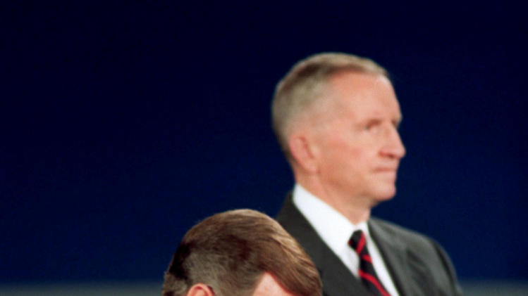 "FILE - In this Oct. 15, 1992, file photo President George H.W. Bush looks at his watch during the 1992 presidential campaign debate with other candidates, Independent Ross Perot, top, and Democrat Bill Clinton, not shown, at the University of Richmond, Va. The ""town hall"" style presidential debates began 20 years ago as a nerve-racking experiment in live television. Moderator Carole Simpson was so nervous about turning over the microphone to regular folks that she spent days mapping out the presidential candidates and their issues on 3-by 5-cards, just in case. Viewers want the candidates to show respect for those voters in the room, who stand in proxy for all Americans. Bush was thrown by a women's oddly and even worse just as she began her question, TV cameras caught Bush checking his watch. That gesture would be replayed over and again as evidence that the president was indifferent and out of touch. ""I took a huge hit,"" Bush said years later. (AP Photo/Ron Edmonds, File)"