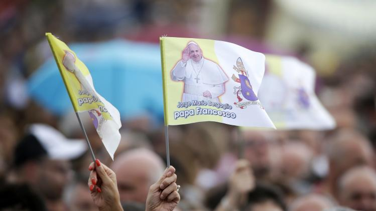Women wave flags with pictures of Pope Francis as they wait for his arrival at the palace of Caserta, former residences of the Royal House of Bourbon, in Caserta