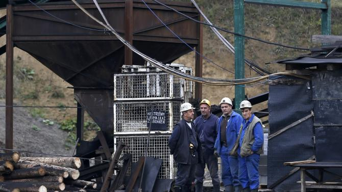 Federal mining inspectors and miners stand near a coal mine entrance near Kakanj