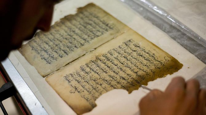 In this photo taken on Monday, Jan. 27, 2014, an employee works on a restoration of an old manuscript at the al-Aqsa mosque compound library in Jerusalem. The library has a collection of some 4,000 old manuscripts with about a quarter considered in poor condition. Half of the books are already undergoing restoration funded by the Waqf, Jordan's Islamic authority which manages the holy site, and with assistance from UNESCO. (AP Photo/Dusan Vranic)