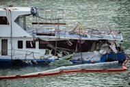 The damaged Lamma IV passenger boat, with the back end of the vessel badly damaged after a collision, is pictured near the shores of Hong Kong&#39;s Lamma island on October 3. Investigators pored over the wreck of the Lamma IV after it was salvaged and dragged onto a beach on Lamma island