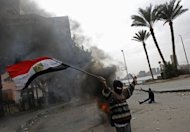 <p>An Egyptian protester waves the national flag as he gestures towards riot police during clashes near Cairo's Tahrir Square on January 28, 2013. In Cairo on Monday, one man was killed as clashes between police and protesters raged into a fifth day.</p>