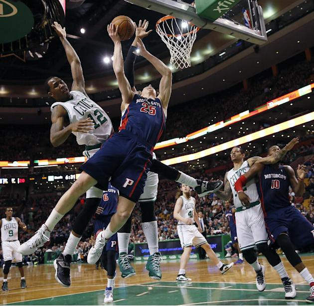 Detroit Pistons' Kyle Singler (25) loses control of the ball in front of Boston Celtics' Chris Johnson (12) in the first quarter of an NBA basketball game in Boston, Sunday, March 9, 2014