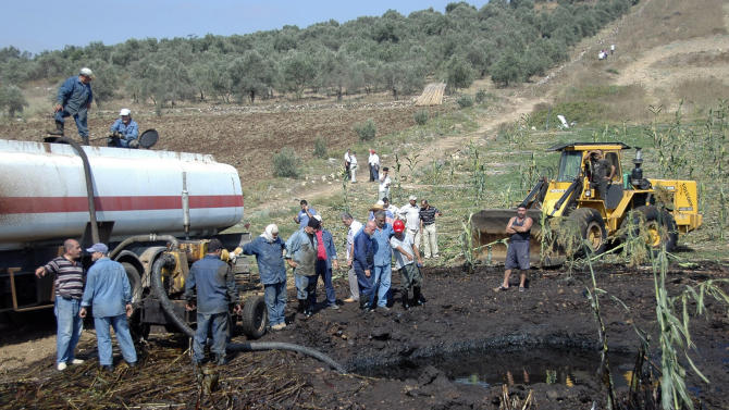 "In this photo released by the Syrian official news agency SANA, workers pump oil from the site of a bomb blast that struck a major oil pipeline in the western town of Talkalakh, Syria, Friday, July 29, 2011. Syrian state television described the blast as a ""terrorist"" attack, saying that a group of ""saboteurs"" was behind the explosion. It was the second incident involving an oil pipeline in a month, and the second time this week that authorities accuse ""saboteurs"" of striking installations. (AP Photo/SANA) EDITORIAL USE ONLY"