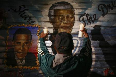 A man holds candles in front of a mural of former South African President Mandela in New York