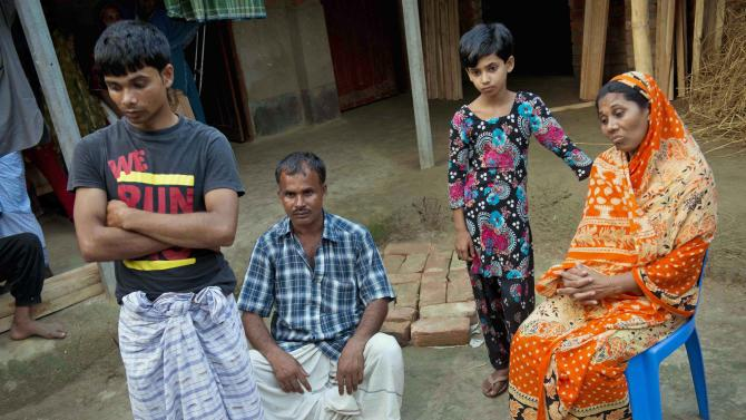 """In this photo taken Tuesday, May 21, 2013, husband and wife Mohammad Razu and Hawa Begum sit with their children Nahid and Asamul outside the family home in Tekani village in far northwestern Bangladesh. They were able to renovate their home using the compensation money they received after their 18-year-old daughter Moushimi was killed along with 111 others trapped behind the locked gates of the Tazreen garment factory when it burned last November. """"Previously we didn't have money but we had peace in our mind. We had a complete family. The peace is no longer there,"""" Hawa said. (AP Photo/Ismail Ferdous)"""