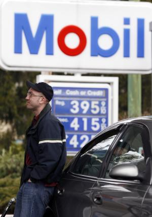 Jeff Hunter of Schenectady, N.Y., pumps gas at a Mobile station in Albany, N.Y., on Friday, March 16, 2012. Higher gas prices slow the economy because they force many consumers to cut their spending on other goods, from appliances and furniture to electronics and vacations.  (AP Photo/Mike Groll)