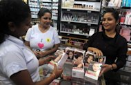An Indian employee of a cosmetic shop displaying L'Oreal products in Siliguri on September 15. Global cosmetic firms are turning to emerging markets in the hunt for sales, but they face a challenge tailoring their beauty products to suit new customers in India, China and elsewhere.