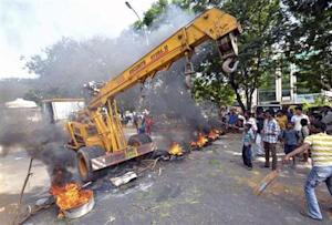 Protesters stop a crane as they block a road with burning tyres during a protest against the creation of Telangana state, at Vizag