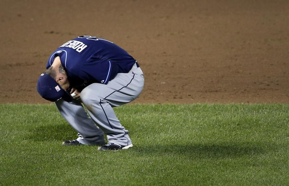 Tampa Bay Rays second baseman Ryan Roberts reacts after hurting his hand while trying to tag out Baltimore Orioles' Nate McLouth at second base in the sixth inning of a baseball game in Baltimore, Tuesday, Sept. 11, 2012. Roberts remained in the game after being examined by members of the Rays staff. (AP Photo/Patrick Semansky)