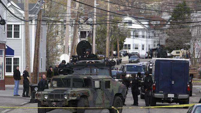 Officials wearing tactical gear stand near an armored vehicle as they search an apartment building for one of two suspects in the Boston Marathon bombing, in Watertown, Mass., Friday, April 19, 2013.  Two suspects in the Boston Marathon bombing killed an MIT police officer, injured a transit officer in a firefight and threw explosive devices at police during a getaway attempt in a long night of violence that left one of them dead and another still at large Friday, authorities said as the manhunt intensified for a young man described as a dangerous terrorist. (AP Photo/Julio Cortez)
