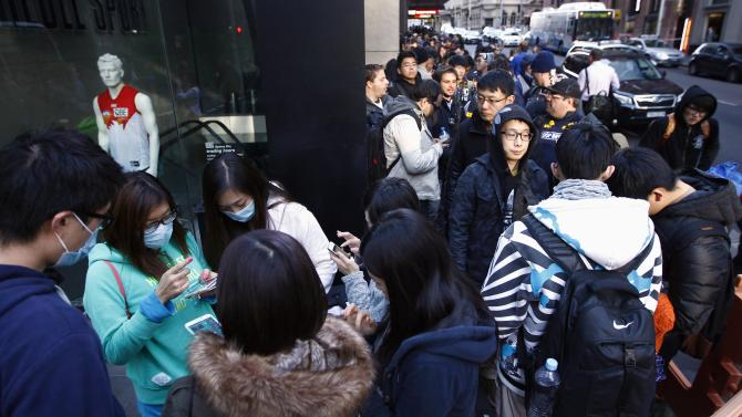 Customers stand in a line outside the Apple store in Sydney on the first day the new iPhone 6 and iPhone 6 Plus went on sale